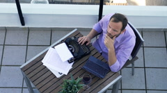 Sad, male writer with typewriter and laptop sitting on terrace, top view Stock Footage