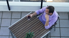 Pensive man waiting and drinking red wine on terrace, top view Stock Footage