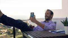 Young, happy man taking selfie photo with cellphone on terrace in country Stock Footage