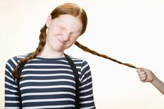 A girl having her pigtail pulled Stock Photos