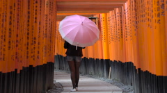 Young woman walking through Torii Gates with umbrella Stock Footage