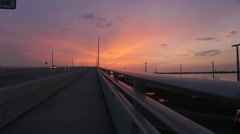Cars speeding by on a bridge in Clearwater Florida at sunset - stock footage