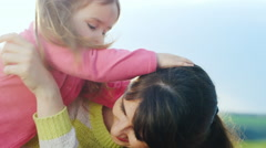 Mother and daughter hugging and playing on the grass Stock Footage