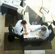 Two businessmen writing on tablecloth Stock Photos