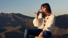 Drunk woman drinking wine while sitting on tree trunk in country Stock Footage