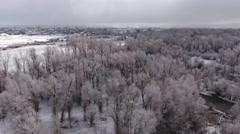 A high aerial shot of a beautiful snowy river and tall trees Stock Footage