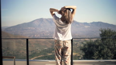 Young woman in pyjamas combing hair on terrace Stock Footage