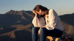 Sad, unhappy woman sitting on trunk tree in country - stock footage