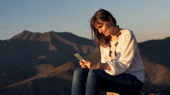 Young, happy woman send sms on smartphone sitting on tree trunk in country Stock Footage