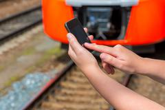Touchscreen mobile phone in female hands on a background of train Stock Photos