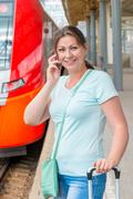girl in a T-shirt and jeans with a suitcase on a journey by train - stock photo
