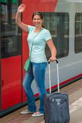 Girl gets on the train and saying goodbye hand - stock photo