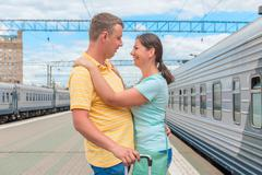 Couple hugging at the train station after a long separation Stock Photos