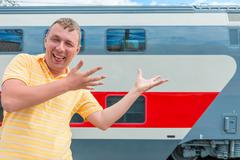 emotional man showing on the double-decker train - stock photo