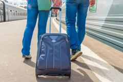 couple with a suitcase embarks on a journey on the train - stock photo