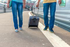 feet walking on the platform passengers with a suitcase - stock photo