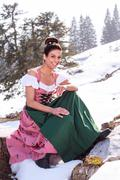 Woman in Dirndl with updo pointing his finger - stock photo