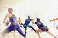Fitness instructor leading exercise class Kuvituskuvat