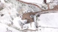 A very high aerial shot over a house and field in winter Stock Footage