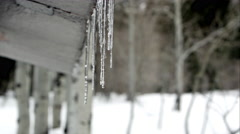 Row of icicles hanging from restroom in the mountains deep in snow. - stock footage