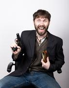 jolly bearded man in a jacket and jeans, sitting on a chair and holding a gun - stock photo