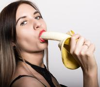 Young amazed woman in lacy lingerie holding a banana, she is going to eat a Stock Photos
