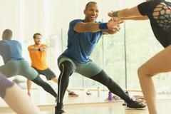 Enthusiastic fitness instructor leading aerobics class Stock Photos