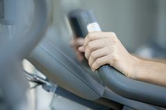 Woman's hands gripping handle of exercise machine, close-up - stock photo
