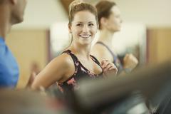 Smiling woman jogging on treadmill at gym Stock Photos