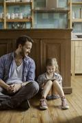 Father looks on as daughter watches amusing video streaming on digital tablet Stock Photos