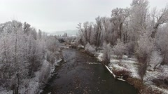 Aerial shot of beautiful snowy river and tall trees Stock Footage