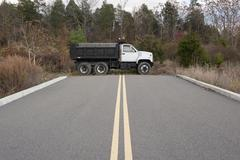 Dump truck parked at dead end on road - stock photo