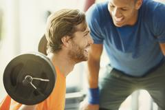 Personal trainer encouraging man doing barbell squats at gym Kuvituskuvat