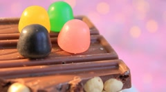 Black Chocolate - orange - green candy on top - pink background Stock Footage