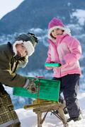 Boy and girl with presents in the snow Stock Photos