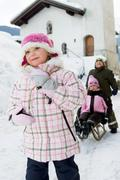 Children playing with sledge in snow Stock Photos