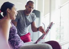 Personal trainer guiding woman on exercise equipment at gym Stock Photos
