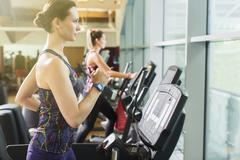 Focused woman running on treadmill at gym Stock Photos
