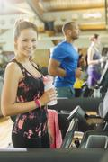 Portrait smiling woman with water bottle on treadmill at gym Stock Photos