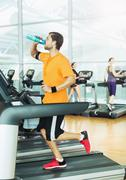 Man drinking water and running on treadmill at gym Stock Photos