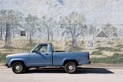 Pick-up truck parked beside wall with mural painted on it - stock photo