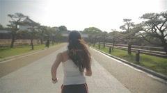 Young Japanese fitness model running in Osaka castle park steadycam follow Stock Footage