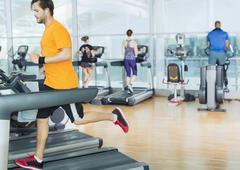 Man running on treadmill at gym Stock Photos