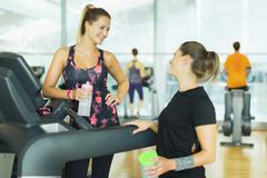 Smiling women resting and talking at treadmill in gym Stock Photos