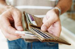 Man removes cash from wallet Stock Photos