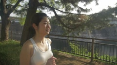 Fun Japanese fitness model running through the park beautiful background Slow - stock footage