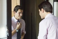 Man looking in mirror, adjusting necktie - stock photo