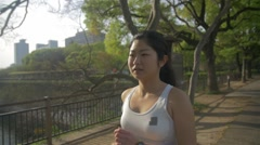 Young Japanese healthy fitness girl running through the park beautiful Stock Footage
