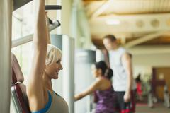 Smiling woman with arms raised using exercise equipment at gym Stock Photos