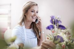 Smiling florist arranging flowers and talking on cell phone Stock Photos
